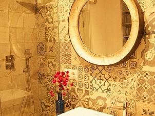 pattern tiles in bathroom - metal round mirror